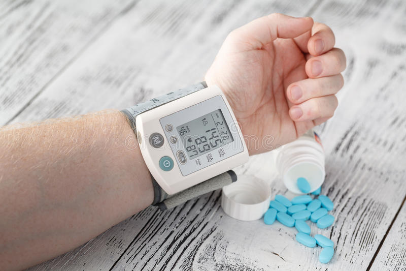 Tonometer wysokiego ciśnienia krwi przejaw na male& x27; s ręka nadciśnienie medyczne pigułki na tle fotografia royalty free