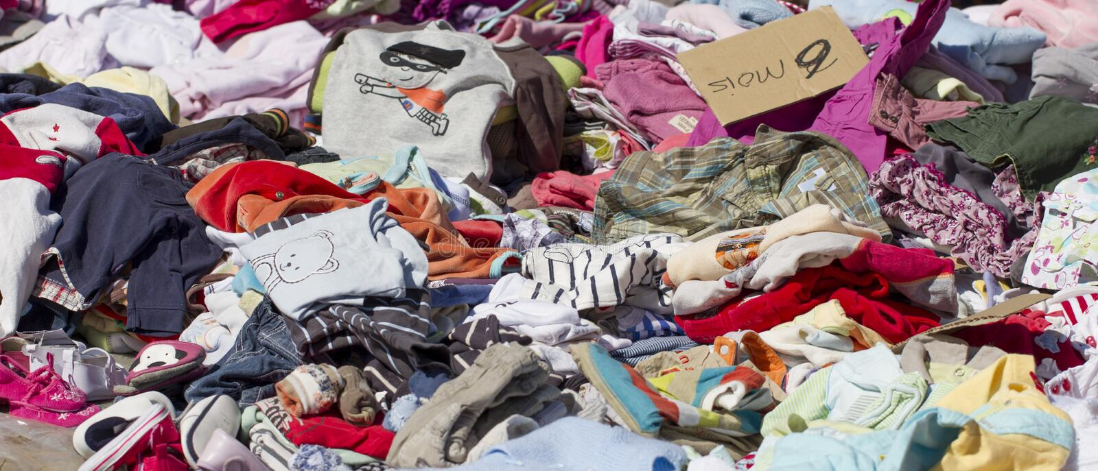 Tons of baby clothes at flea market royalty free stock photos
