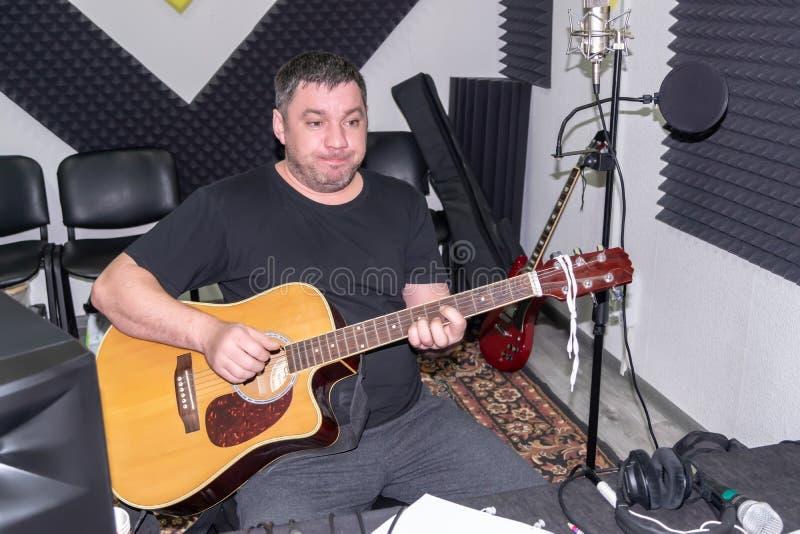 Tonstudio des Mannes zu Hause mit einer Gitarre in seinen Händen lizenzfreie stockfotografie