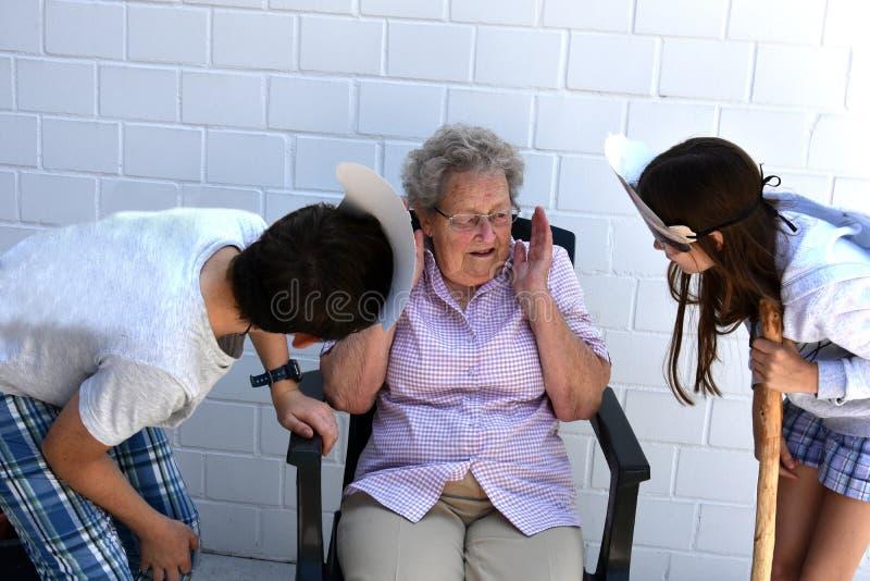 Tonto de los adolescentes alrededor con su abuela foto de archivo