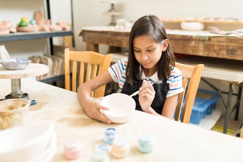 Tonwaren-Studenten-Painting Bowl With-Bürste bei Tisch stockfotos