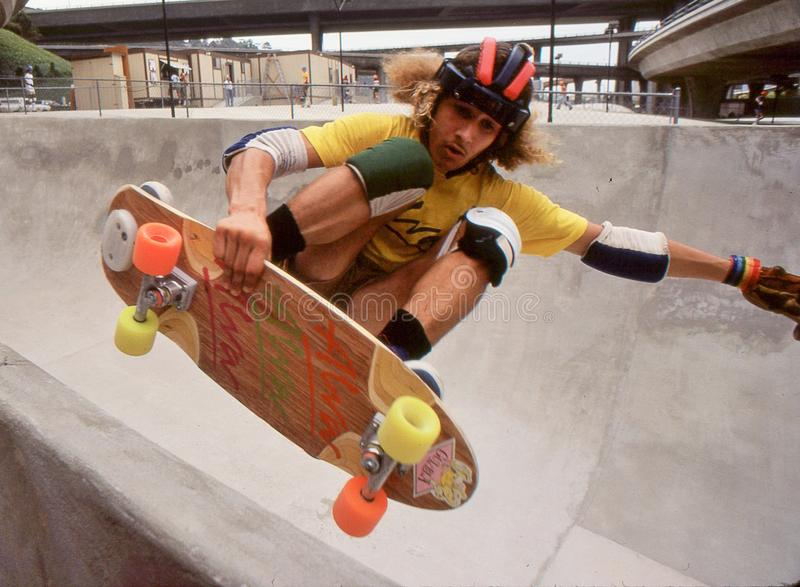 Tony Alva in the half pipe catching air at Oasis. Tony Alva grabbing his board and catching air while riding the half pipe at Oasis Skate Park in San Diego stock image