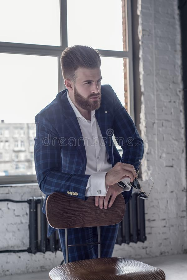 Too good to be real. Good looking young man in full suit holding eyewear and looking away while sitting on the stool royalty free stock photos