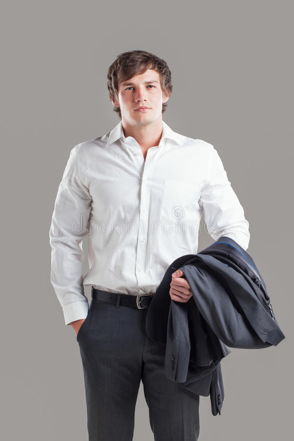 Too hot for business. A serious looking business man with his hand in his pocket and his gray suit jacket flung over his arm royalty free stock photos