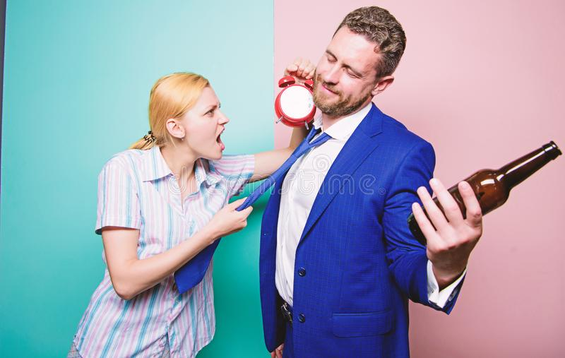 It is too late. Angry wife meeting drunk husband late at home. Man suffering from alcoholism. Businessman with alcohol. Bottle and woman with alarm clock stock photography