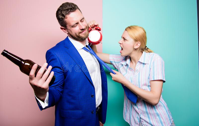 It is too late. Angry wife meeting drunk husband late at home. Man suffering from alcoholism. Businessman with alcohol. Bottle and women with alarm clock stock image