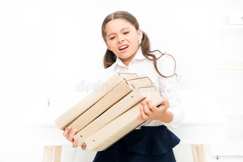 Too much information. kid learn and study hard. back to school. upset girl with workbook folders. Education. heavy. Documents. Towards knowledge. small girl in stock photography