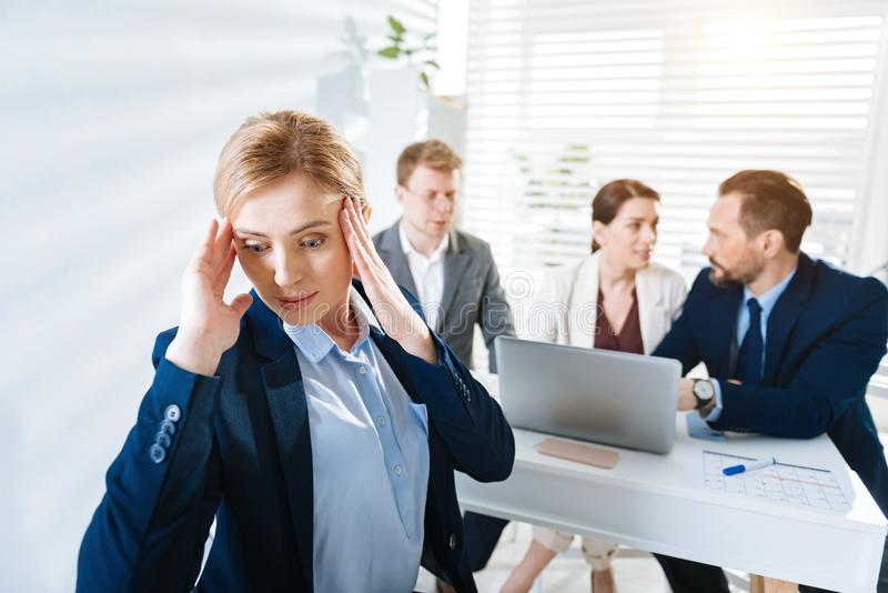 Upset female colleague experiencing stress at work royalty free stock photography