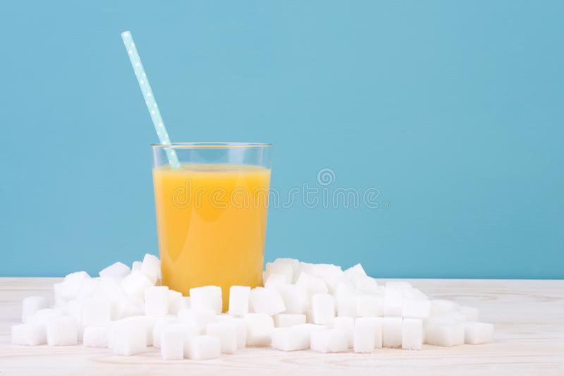 Too much sugar in drinks concept. Glass of orange juice with plenty of sugar cubes on white table and blue background. Too much sugar in drinks concept stock photography