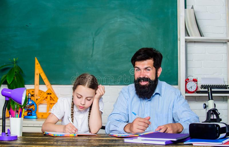 Too much work. private lesson. knowledge day. Home schooling. daughter study with father. Teachers day. small girl child. With bearded teacher men in classroom royalty free stock photo