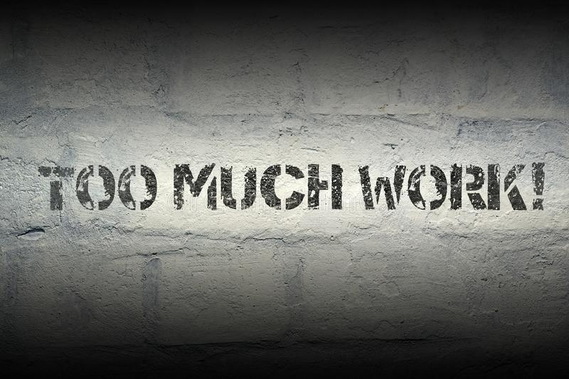 Too much work gr. Too much work stencil print on the grunge white brick wall stock photography