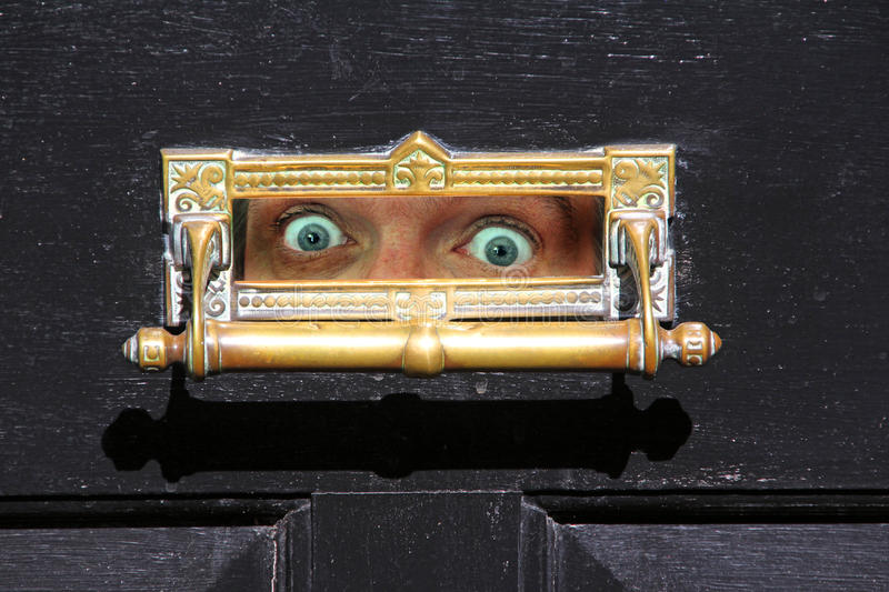 Too scared to open the door!. Photo of someone peeping through the letterbox too scared to open the door and venture outside royalty free stock image