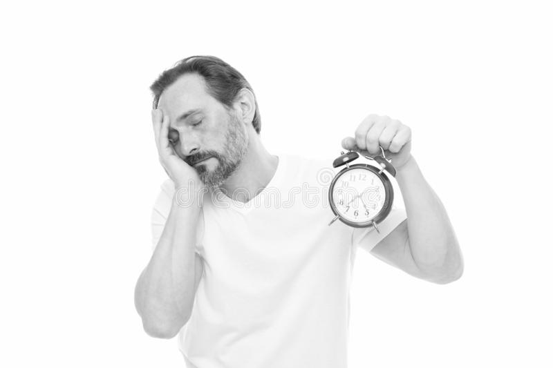Too tired for early awakening. Man hold alarm clock in hand. Guy bearded man do not care about time left. Time royalty free stock photo
