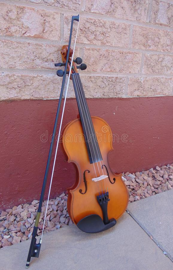 Violin against brick wall of house. Took a beautiful picture of my violin against the wall outside of my house in the Summertime stock photography