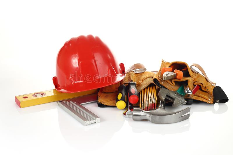 Tool belt with hand tools. And red helmet royalty free stock photos