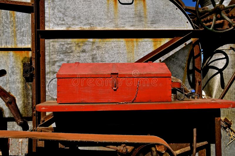 Tool box on an old threshing machine. An old red wood handmade toolbox resides on a ledge of a vintage threshing machine stock photos