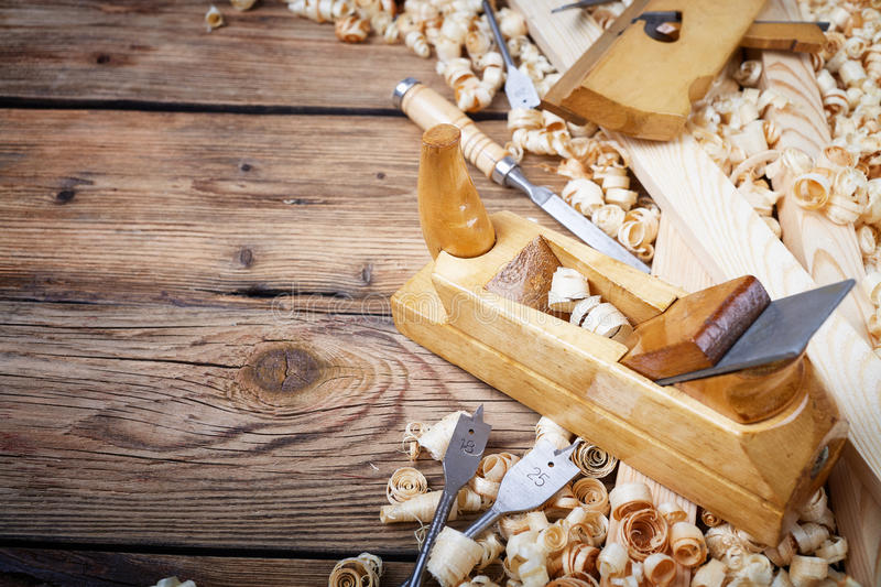 Tool in carpenter`s workshop. Wooden planer, table from old wood, natural building materials, woodwork and antique hand tools, carrying out carpentry, tool kit royalty free stock photos