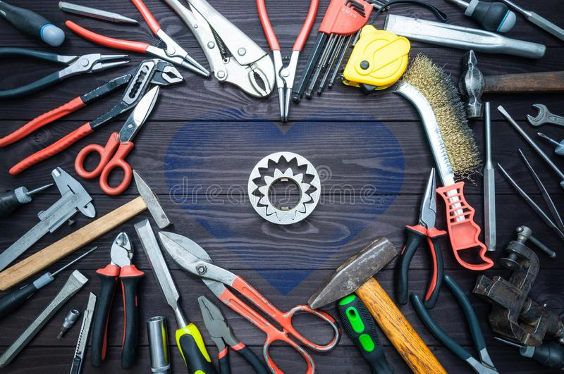 Tool and heart on dark wooden background. Love for your work, Father`s Day. Tool and heart on a dark wooden background. Concept Love for your work, Father`s Day royalty free stock images