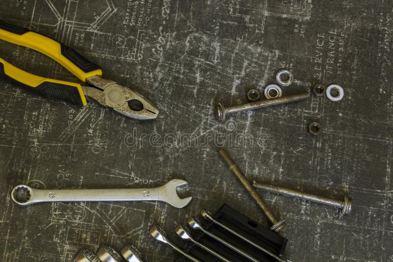 Tool set of pliers, wrenches, bolts and nuts on abstract grey surface. Tool set of pliers, different wrenches, bolts and nuts on abstract grey surface royalty free stock image