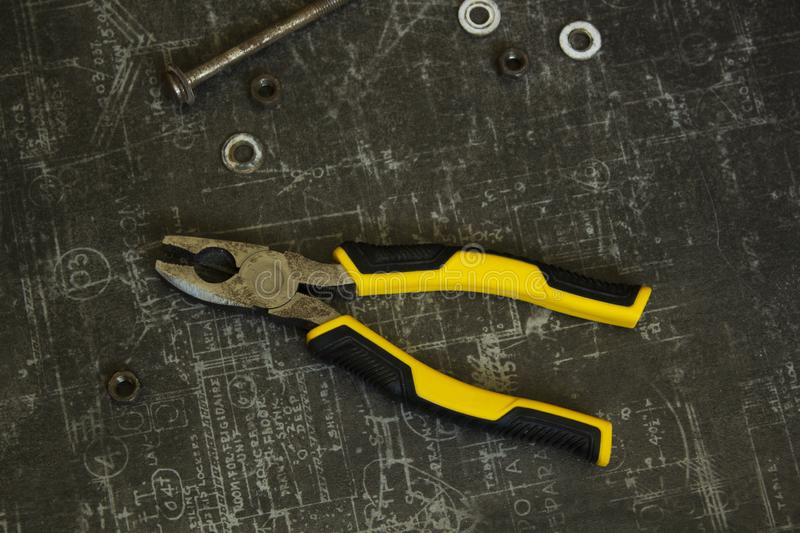 Tool set of pliers, wrenches, bolts and nuts on abstract grey surface. Tool set of pliers, different wrenches, bolts and nuts on abstract grey surface royalty free stock photos