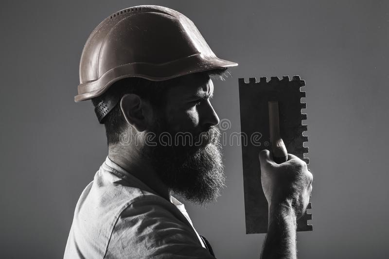 Tool, trowel, handyman, man builder. Mason tools, builder. Bearded man worker, beard, building helmet, hard hat stock photo