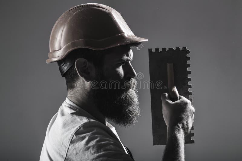 Tool, trowel, handyman, man builder. Mason tools, builder. Bearded man worker, beard, building helmet, hard hat. Builders in hard hat, helmet Mason plastering stock photo