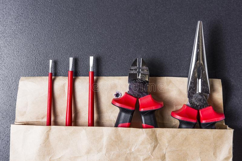 Tool for working screwdriver, pliers, platypuses. Tools electrician on a black background. stock images