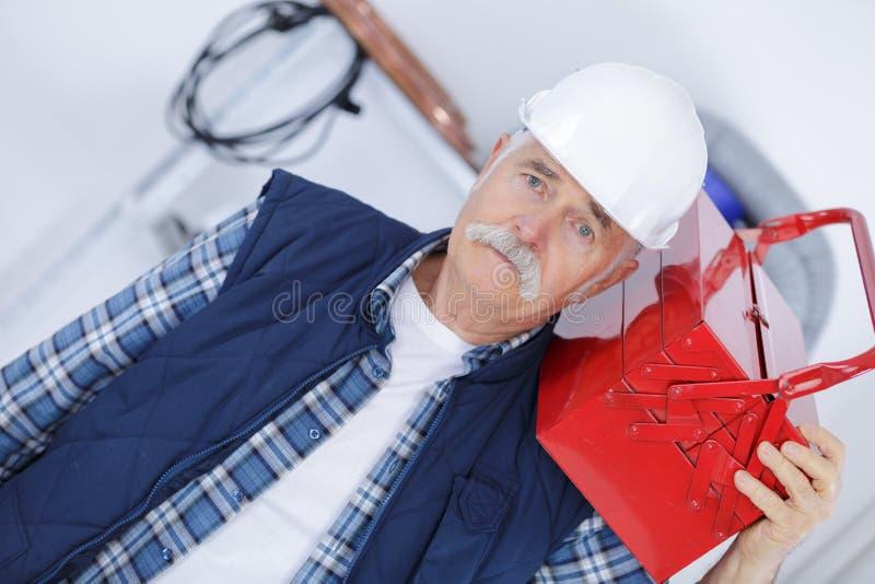 Toolbox нося старшего человека на плече стоковые фото