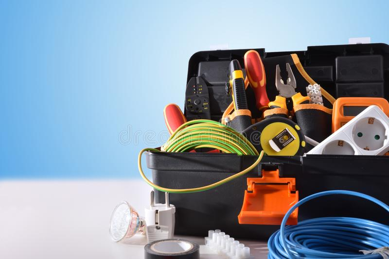 Toolbox full of tools and electrical equipment on white table. And blue isolated background. Front view. Horizontal composition stock photography