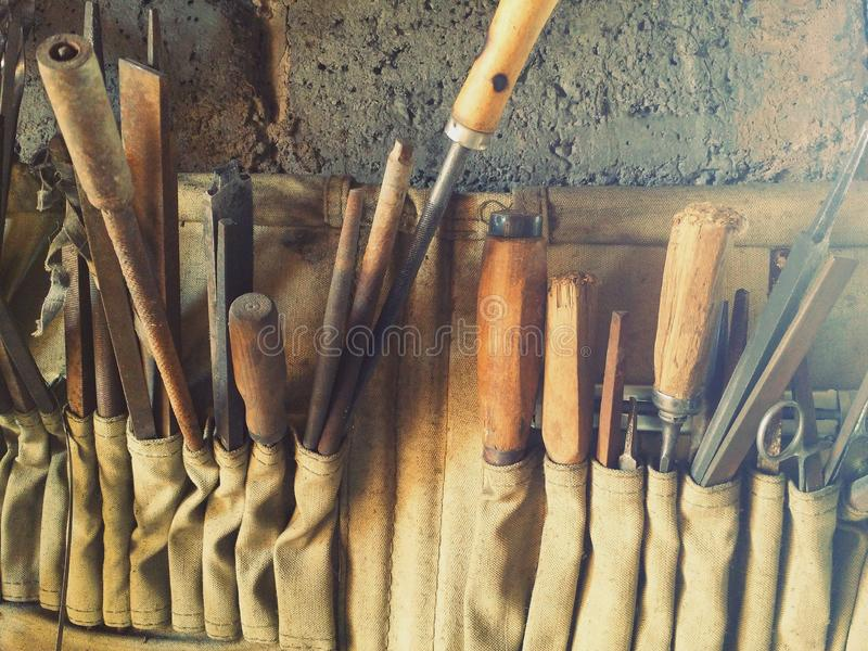 Tooling in old dirty beige rag rack on concrete wall royalty free stock photography