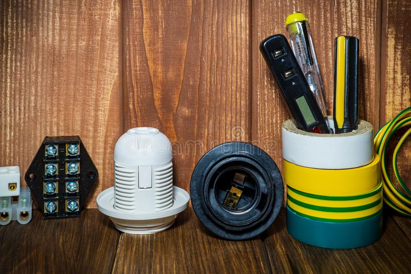 Tools and accessories used in electrical installations. Tools and accessories on a vintage wooden background used in electrical installations royalty free stock image