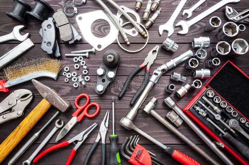 Tools and auto spare parts on wooden workbench royalty free stock images