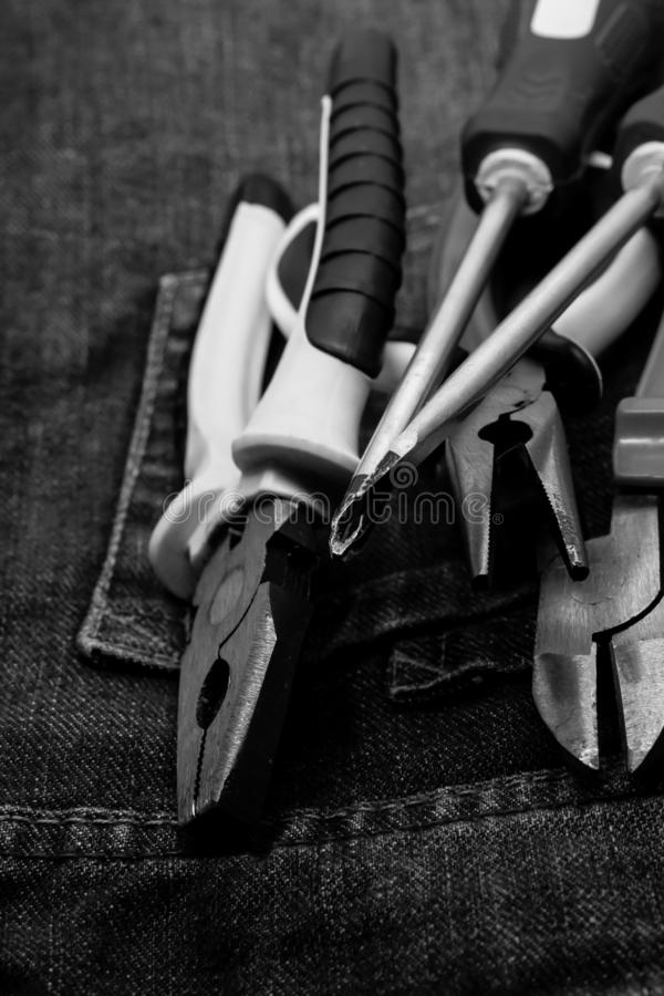 Tools on the background of work clothes. vertical monochrome photo. Mites and pliers royalty free stock photos