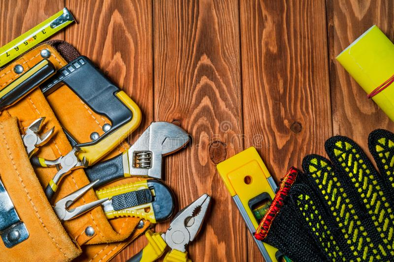 Tools in the bag for master builder prepared before work on a brown wooden boards stock photo