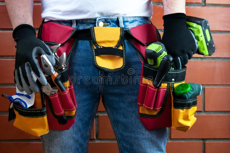Tools in the belt for tools. The builder is holding an electric screwdriver. Selective focus. royalty free stock images