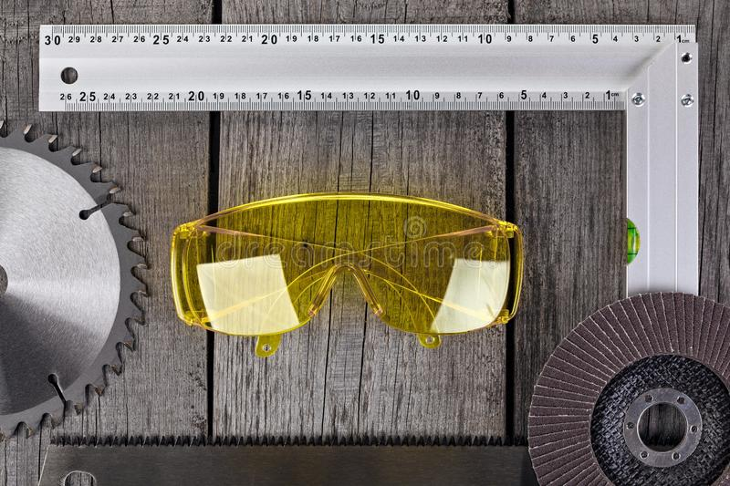 Tools for carpentry work, measurement of parts and eye protection on a wooden background.  stock photos
