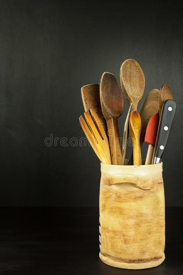 Tools cook on a wooden shelf. Kitchen utensils in a ceramic container on black background. royalty free stock photos