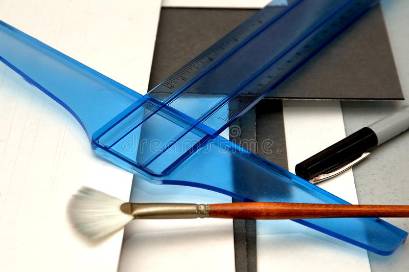 Tools for cutting matboard to frame artwork. A t-square, matboard, fan brush and pen, all tools used to mat and frame artwork stock photos