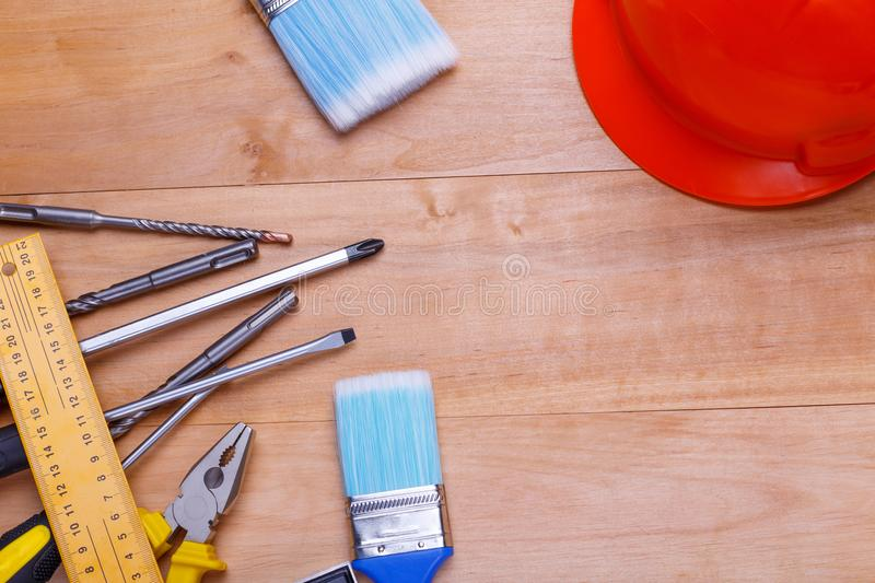 Tools in the left corner and drills with a helmet on the right on a wooden background. View from above. Tools are different screwdrivers, pliers, corner, brushes stock image