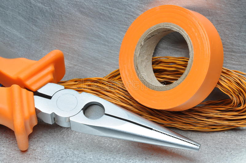 Tools and electrical component on metal surface. With place for text stock image
