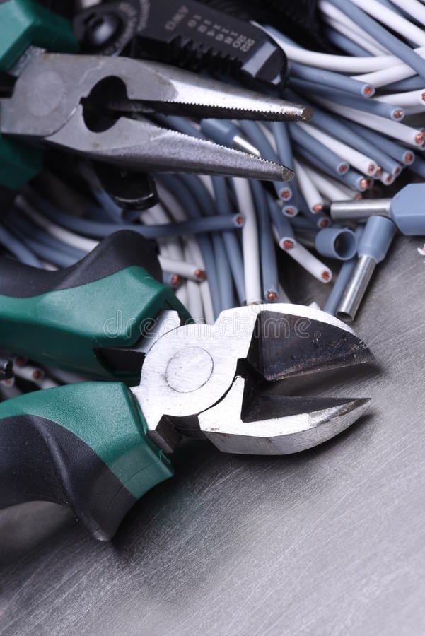 Tools for electrician and cables. On grey metal surface royalty free stock images