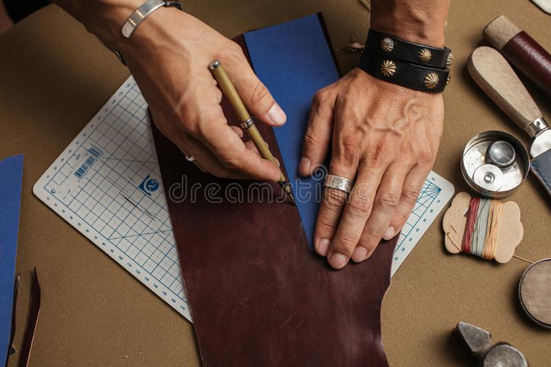 Working process of producing hand made leather wallet in the leather workshop. Tools and equipment for leather handmade goods. Cropped image of a male artisan stock photo