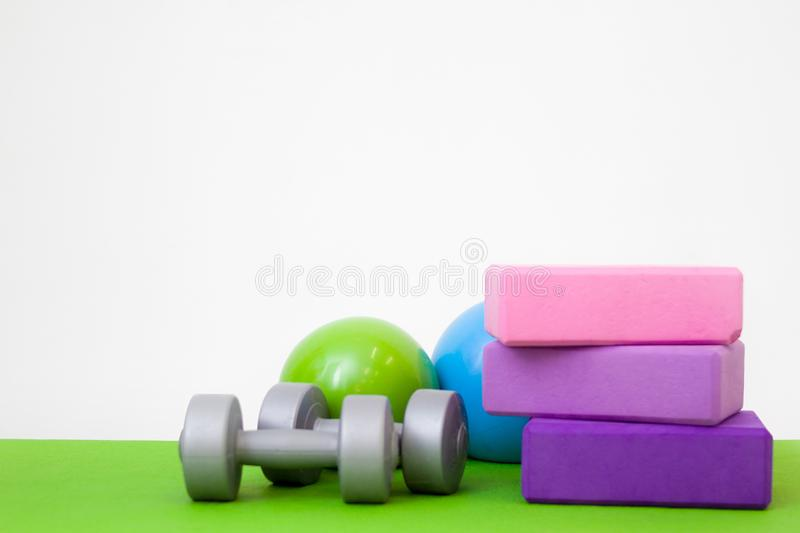 Tools for fitness exercises - pink and purple blocks, balls and dumbbell on green mat. free space for text - gymnastic, stretching stock photos