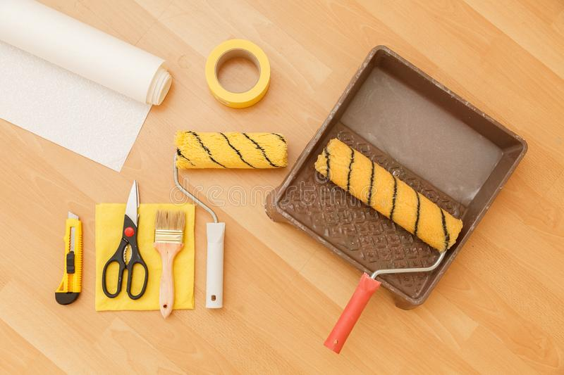 Tools for gluing wallpapers. Renovation. Tools for gluing wallpapers. A room after renovation. Fresh repair in a room. Floor from laminate stock photo