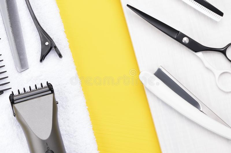 Tools for hair cutting lie on a white towel on a yellow background stock image