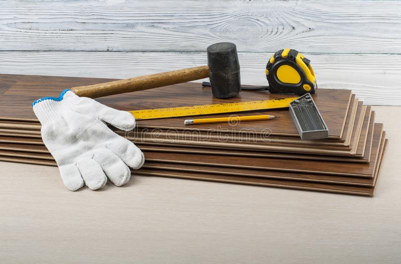 Carpentry concept. Different tools and gloves on the new laminate flooring.Copy space for text. stock photos
