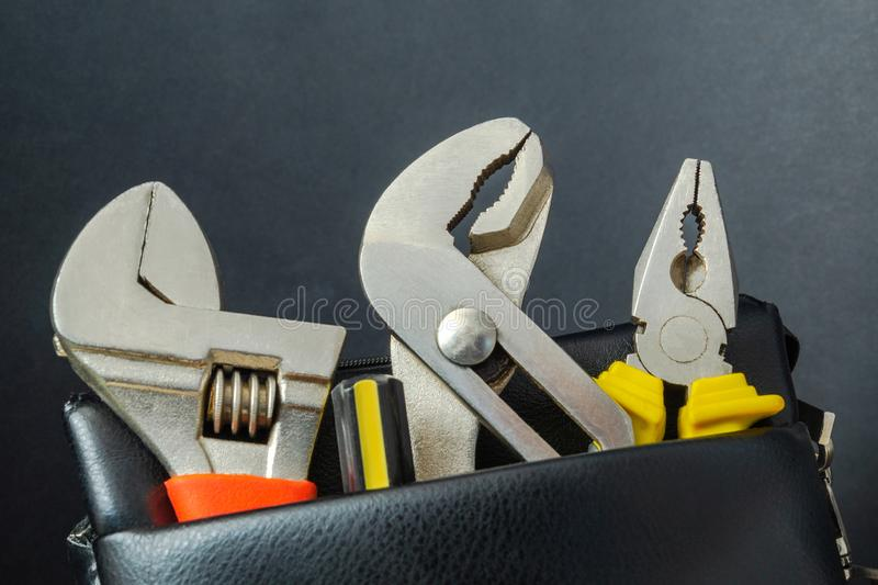 Tools in a leather bag on a black background - wrenches and pliers royalty free stock images