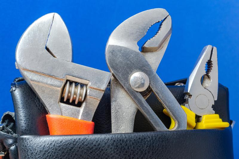 Tools in a leather bag on a blue background - wrenches and pliers stock photography