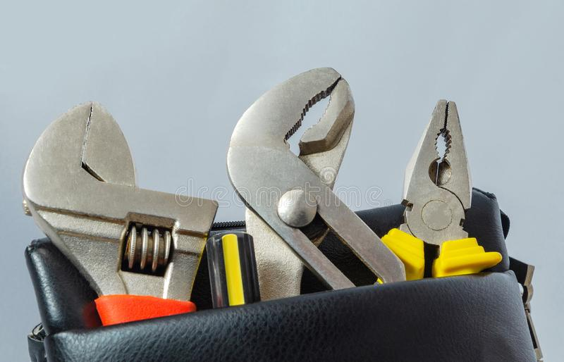 Tools in a leather bag on a gray background - wrenches and pliers royalty free stock images