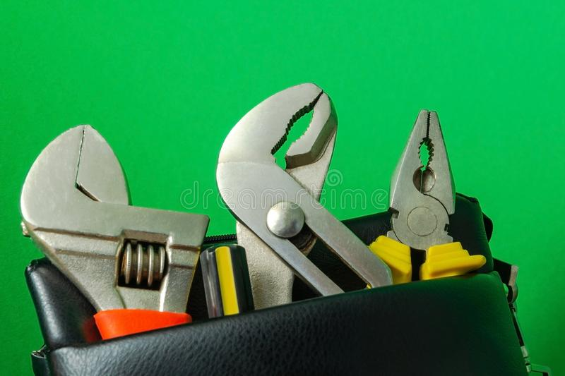 Tools in a leather bag on a green background - wrenches and pliers royalty free stock photo